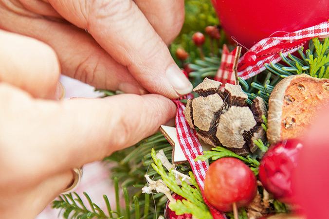 Bänder und andere zarte Deko befestigt man besser mit Stecknadeln auf dem Adventskranz