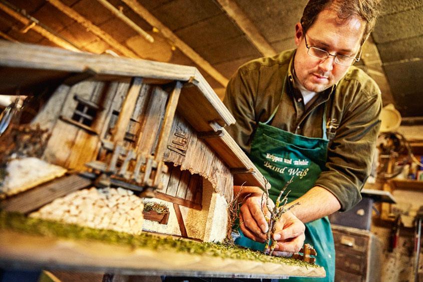 Krippenbauer setzt einen Baum vor seinen gebauten Stall