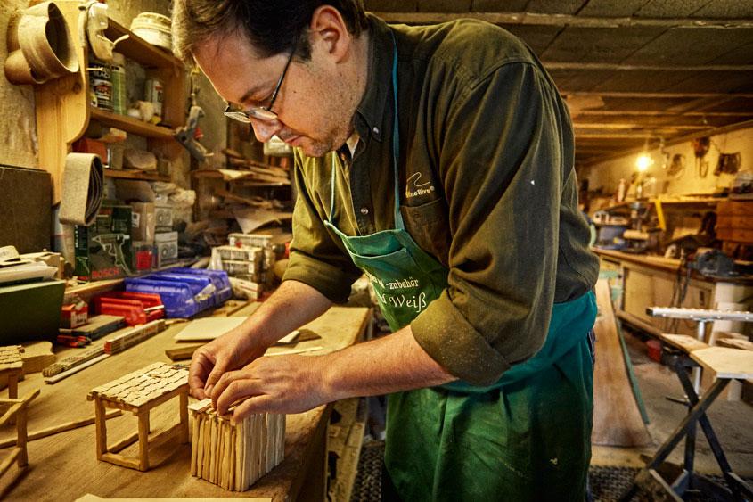 Krippenbauer baut aus kleinen Holzstäben ein Dach für den Schuppen seiner Krippe