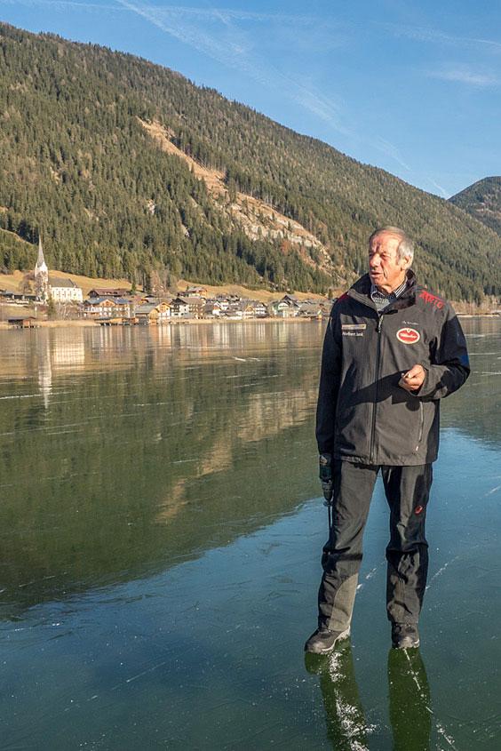 Der Eismeister vom Weißensee steht auf spiegelblankem Eis
