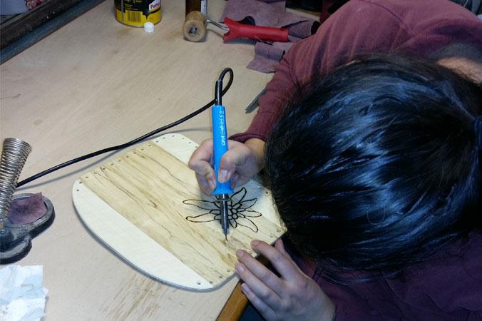 Handtaschen aus Holz: Frau brennt Muster ein