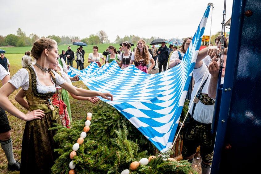 Die Bayernfahne wird von Mädels gehalten während ein junger Mann die Fahne am Maibaum befestigt