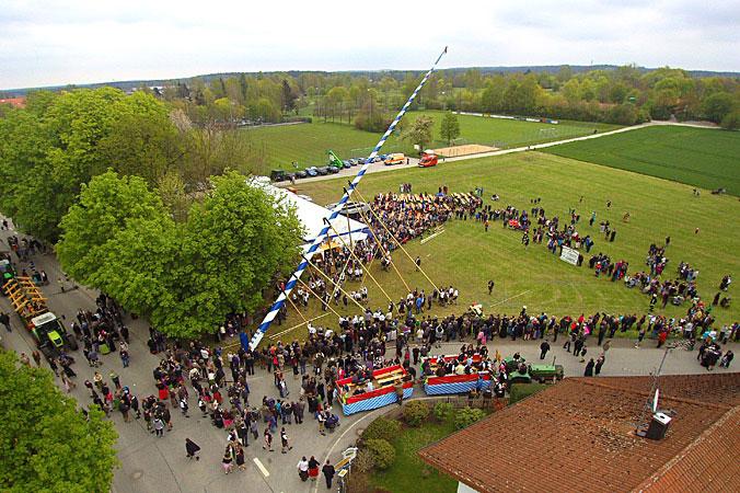 Der Maibaum wird aufgestellt und viele Menschen schauen zu