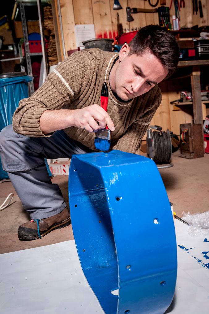Eine Eisenschelle des Maibaums wird blau bemalt