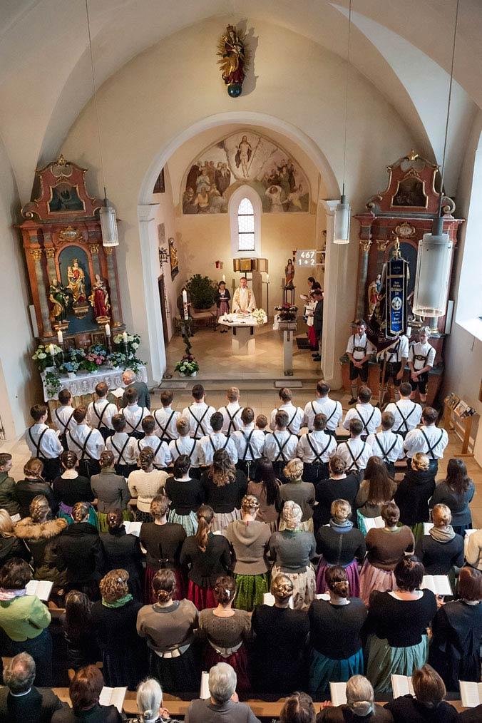 Mehrere Menschen in Tracht nehmen am Maibaum-Gottesdienst Teil