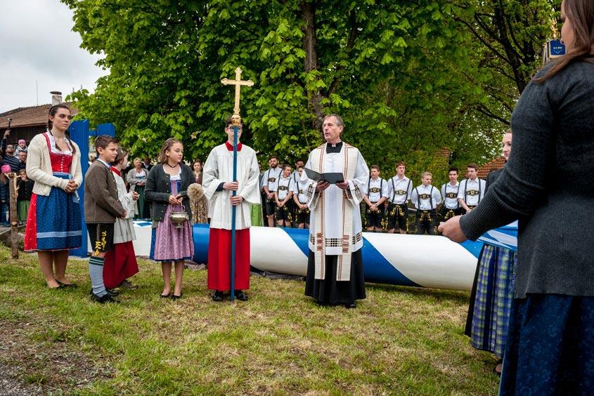 Der Maibaum wird von einem Pfarrer gesegnet