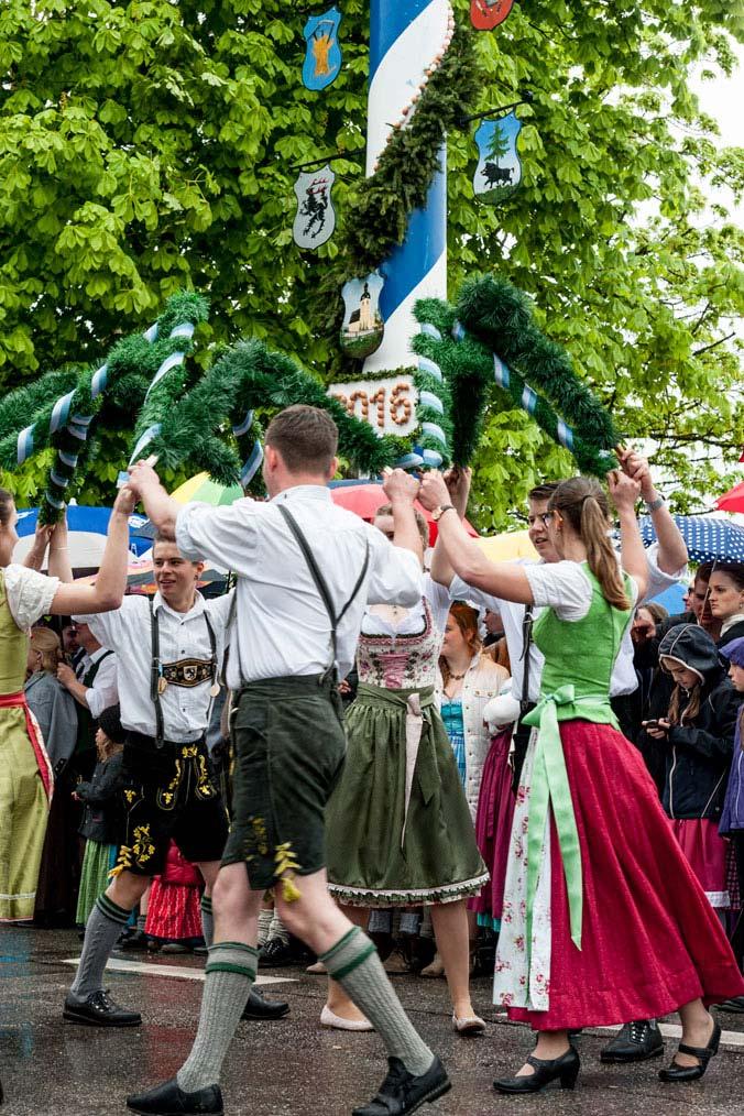 Burschen und Madln tanzen in Tracht den Maibaumtanz