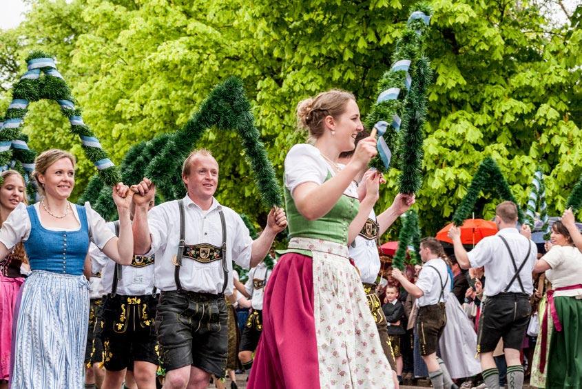 Mehrere Menschen tanzen fröhlich in bayerischer Tracht den Maibaumtanz