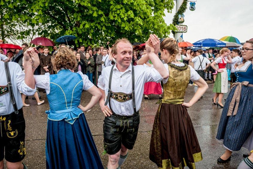 Mehrere Menschen tanzen in bayerischer Tracht den Maibaumtanz während es regnet