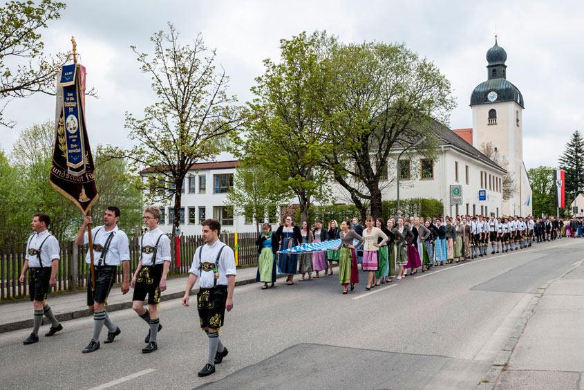 Madeln und Burschen ziehen von der Kirche aus in einer festlichen Prozession zum Maibaumplatz
