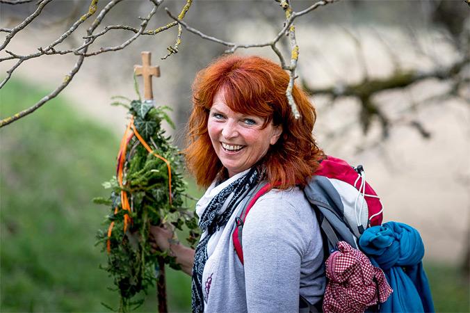 Vierbergelauf – eine Pilgerin mit Wanderstab und Kräutern