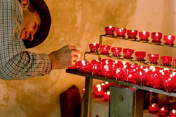 Vierbergelauf – Ein Pilger zündet ein Opferlicht an