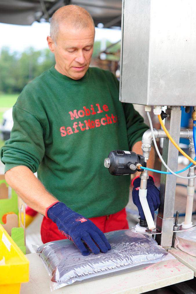 Apfelernte am Bodensee – Rainer Bauer füllt den Apfelsaft in Beutel ab