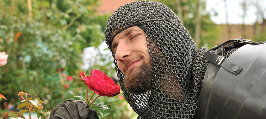 Ritter in schwarzem Kettenhemd riecht an einer Rose