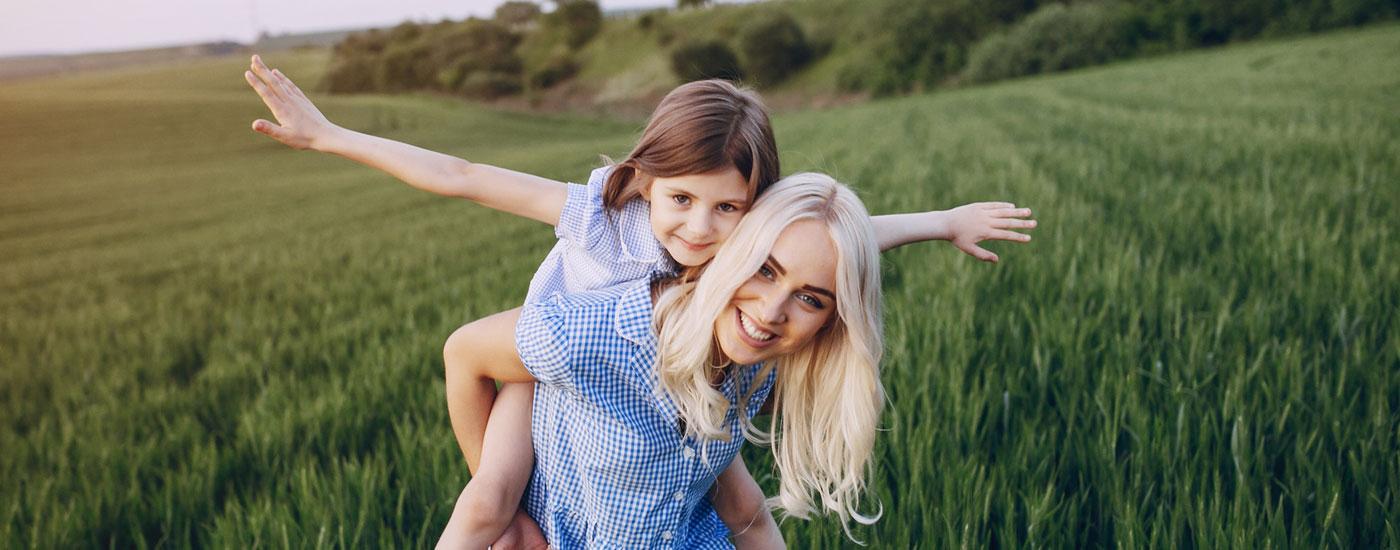Mutter mit Tochter auf dem Rücken in einem Feld