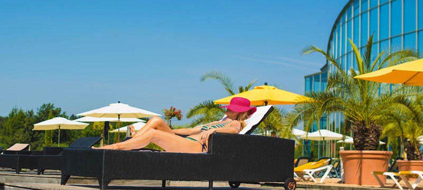 Frau mit Sonnenhut und Bikini auf einer Sonnenliege mit Palmen im Hintergrund