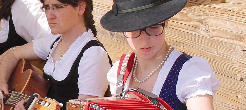 Zwei Frauen in Tracht vor einer Hütte musizieren an Gitarre und Ziehharmonika