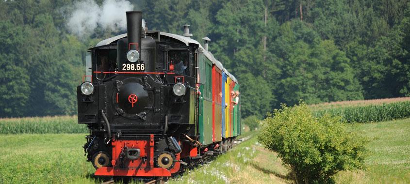 Zug mit bunten Waggons wird von einer Dampflok gezogen