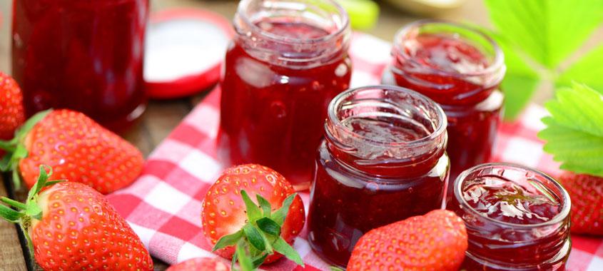 Erdbeer-Rezepte: Erdbeeren und mit Erdbeermarmelade gefüllte Gläser auf Tischdecke