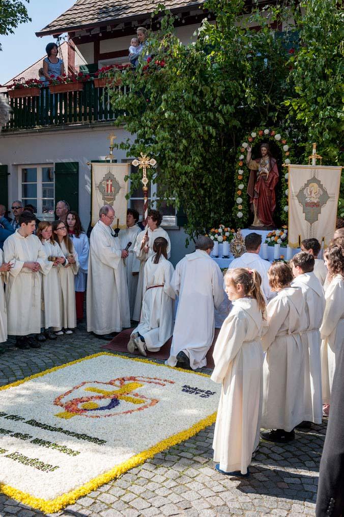 Priester, Ministranten und Volk versammeln sich um den Blumenteppich