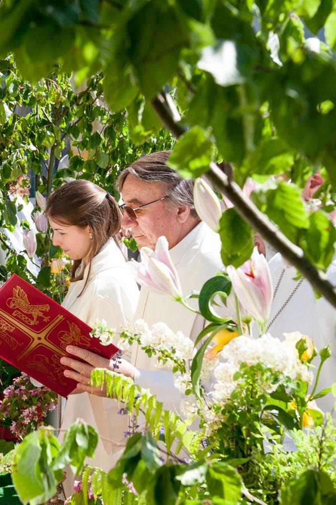 Priester liest aus einem roten Buch