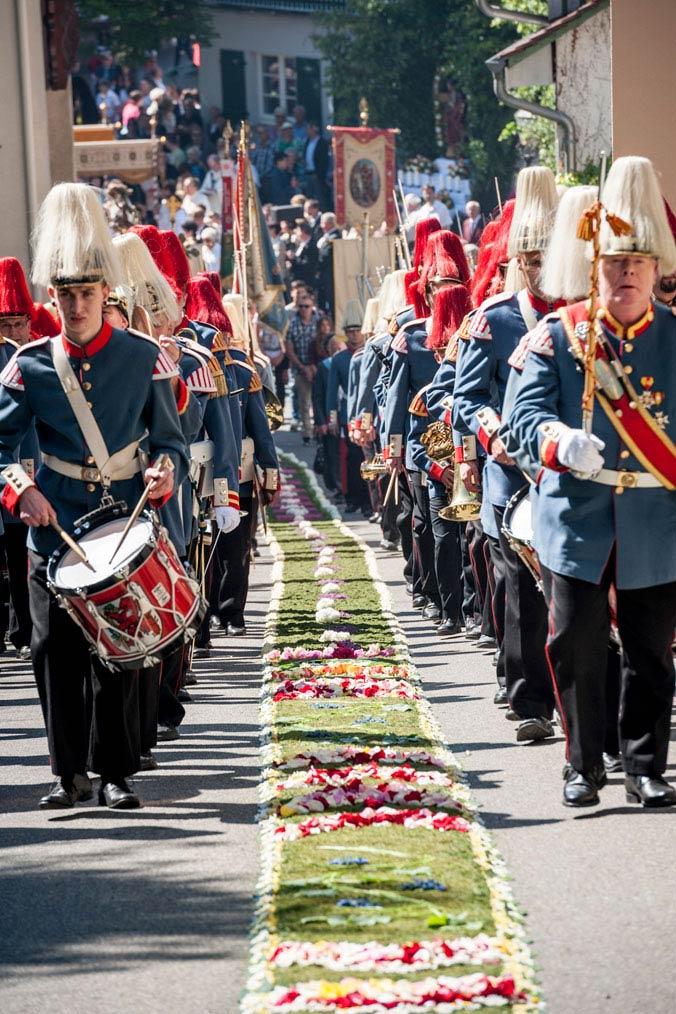 Musikkapelle läuft rechts und links des Blumenteppichs