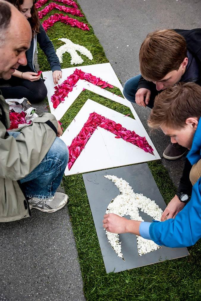 Zwei Kinder und ein Erwachsener legen mithilfe von Schablonen bunte Blumen auf einen Grasteppich