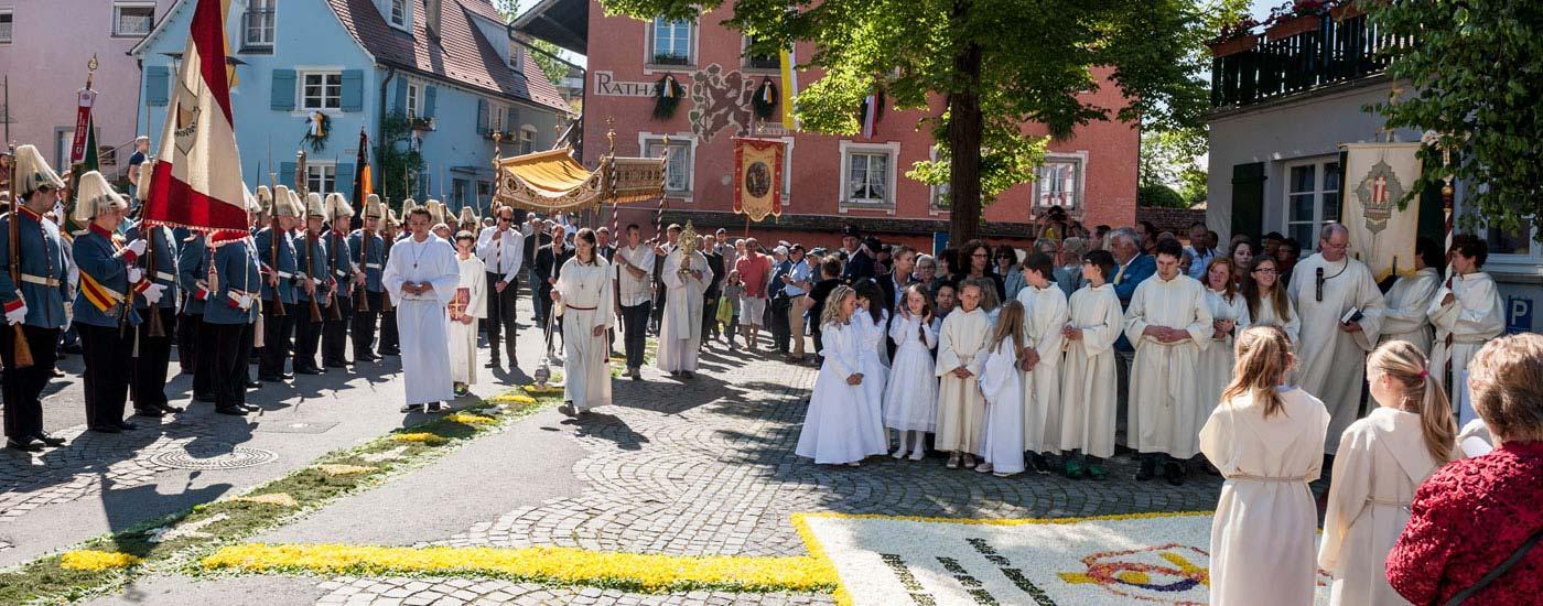 Fronleichnamsprozession mit Pfarrer, Ministranten, Musikkapelle und Volk