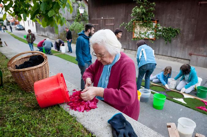 Eine ältere Dame schneidet die Blumen zurecht.