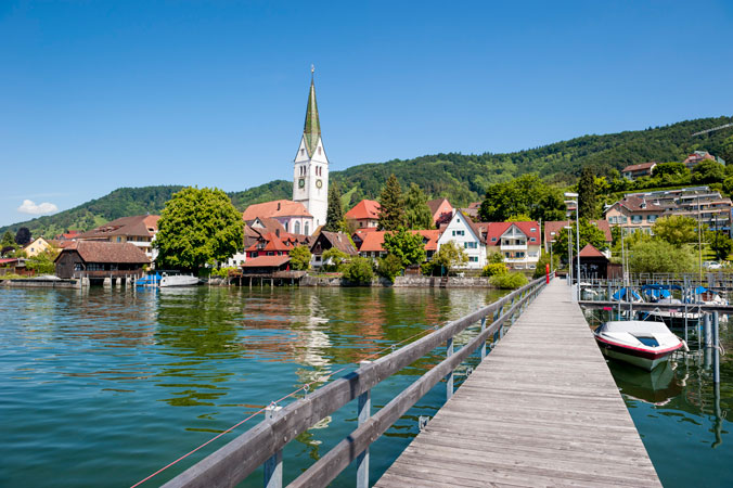Steg im Bodensee mit Stadt im Hintergrund