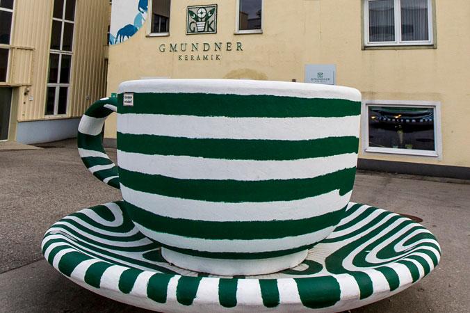Vor dem Eingang zur Gmundner Keramik Manufaktur steht eine rießige Kaffeetasse mit dem typischen grüngeflammten Design