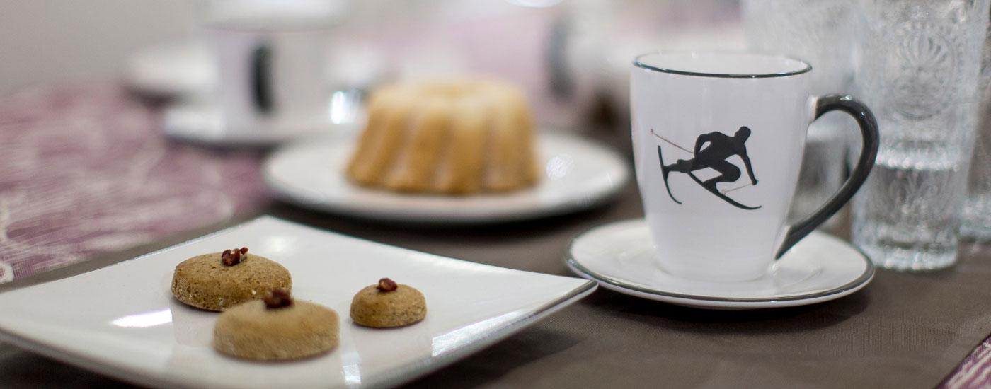 Ein gedeckter Kaffeetisch mit Geschirr von Gmundner Keramik und der Tasse mit Skifahrer Toni
