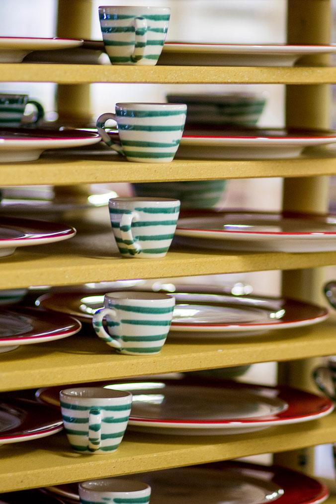 Fertig bemalte Tassen und Teller stehen im Regal