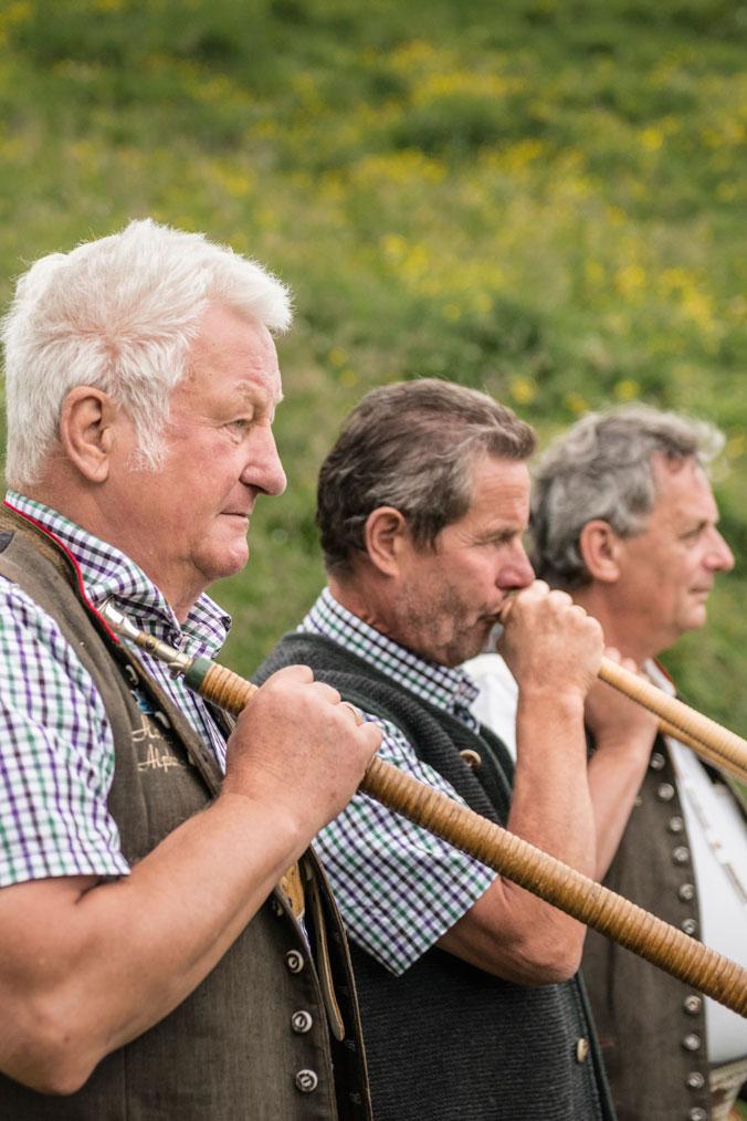 Hundstoa-Ranggeln – Drei Alphornbläser mit Instrumenten