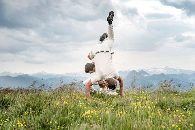 Hundstoa-Ranggeln – Zwei Männer ranggeln miteinander auf der Wiese
