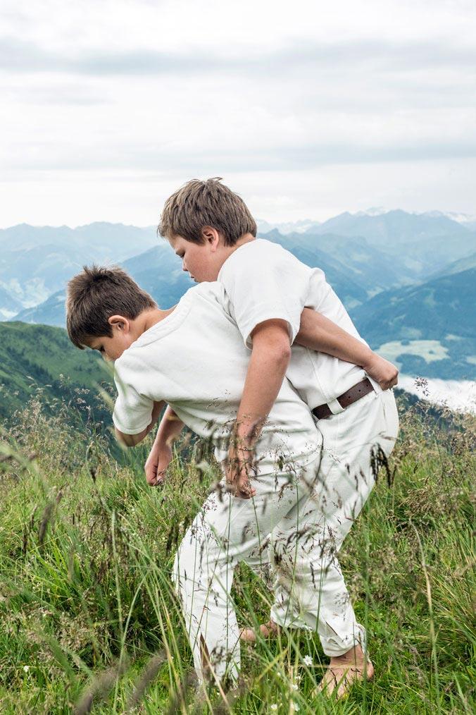 Hundstoa-Ranggeln – Zwei Kinder beim Ranggeln auf der Wiese