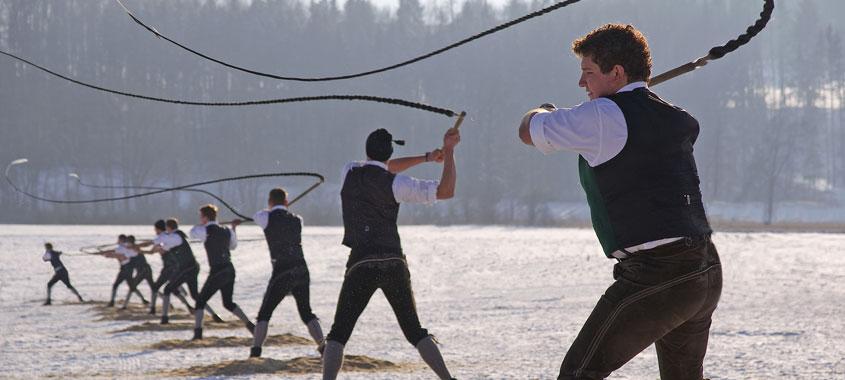 Januarbräuche-Burschen in Tracht schwingen bis zu 4 Meter lange Peitschen