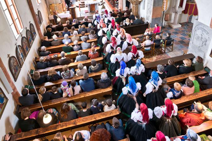 Frauen mit Kopftüchern ziehen in eine voll besetzte Kirche ein