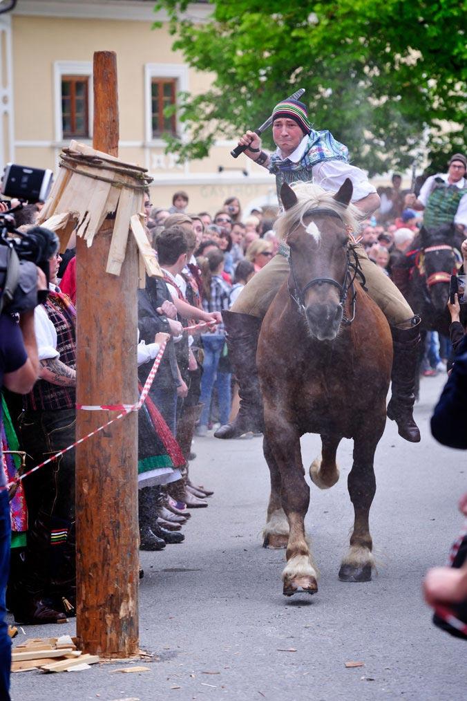 Mann auf Pferd reitet mit einer Keule in der Hand auf einen Holzpflock zu