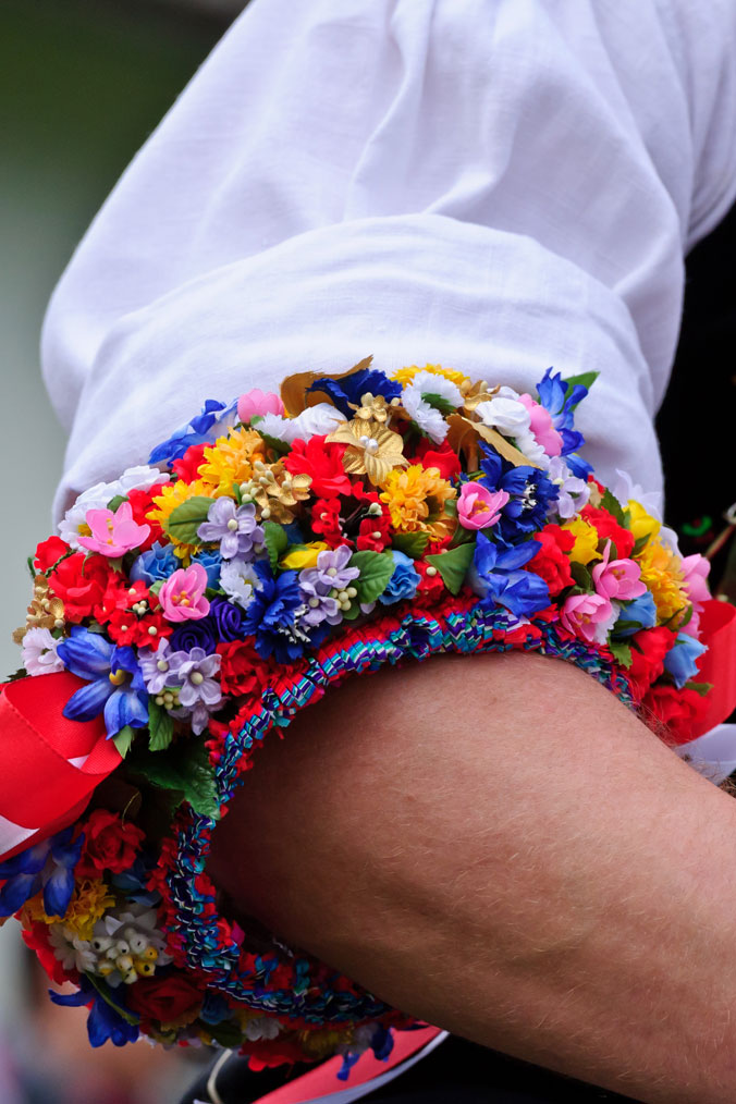 Bunter Blumenkranz um den Oberarm eines Mannes