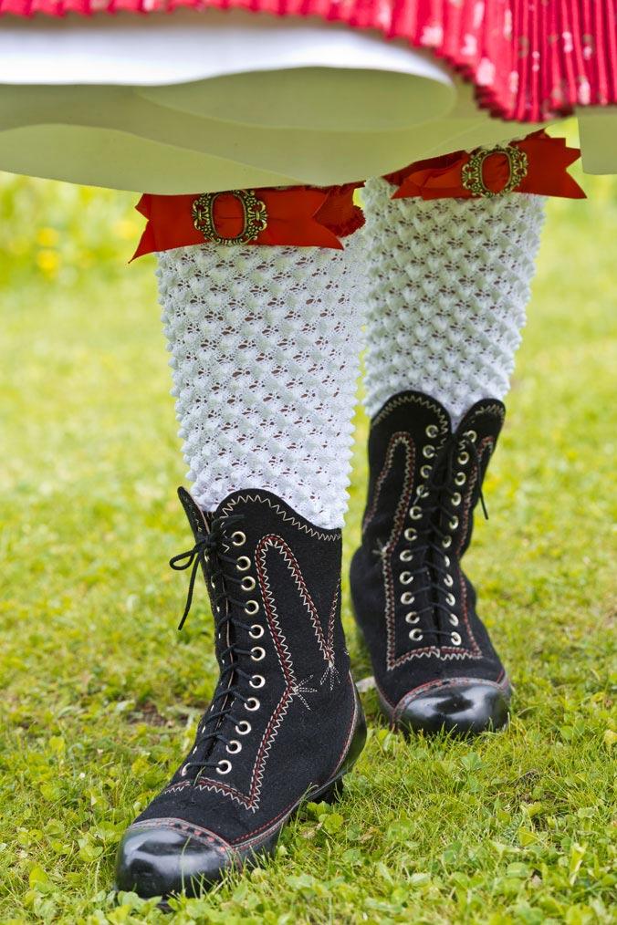 Frauenbeine mit weißen Strümpfen und schwarzen Schnürstiefeln