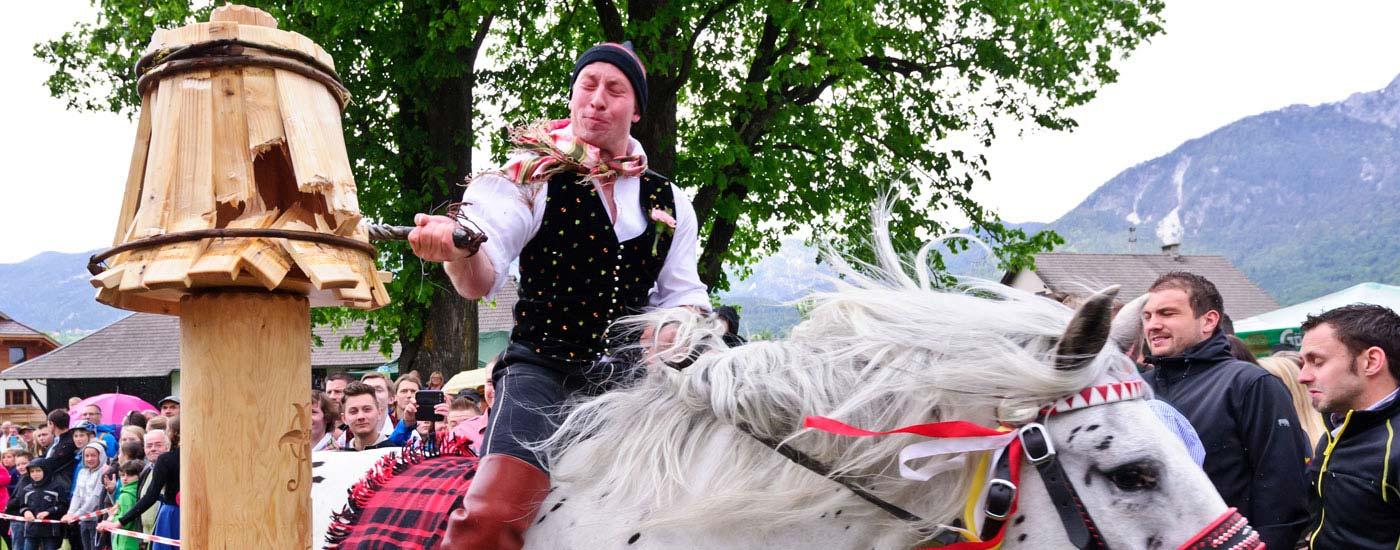 Ein Bursche in Tracht reitet auf einem Pferd und zerschlägt den Kufen beim Kufenstechen in Feistritz