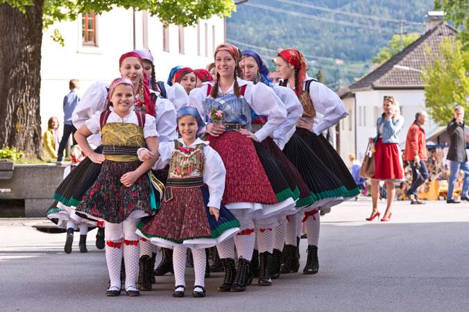 Beim Kufenstechen stehen junge Mädchen in Gailtaler Tracht in zwei Reihen auf einem Dorfplatz