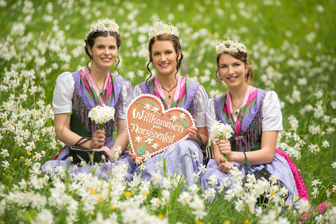Die drei Narzissenhoheiten Brigitte Maier, Lisa Streußnig und Maria Benischek sitzen in einer Wiese mit blühenden Narzissen