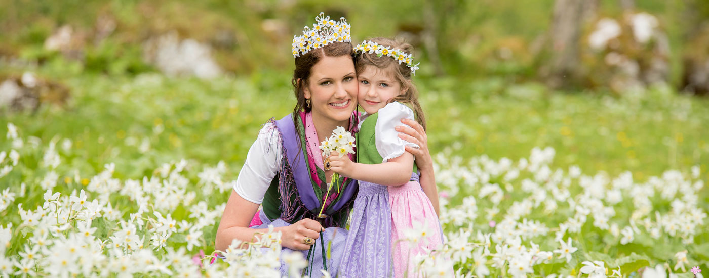 Narzissenfest Bad Aussee 2017 – Die Narzissenkönigin Brigitte Maier in mitten von blühenden Narzissen mit einem Blumenkind