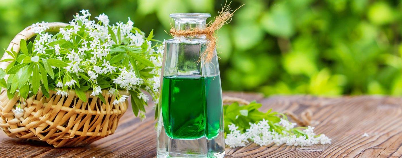 Korb mit Waldmeister und Flasche mit grüner Maibowle auf einem Holztisch