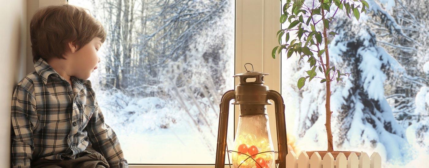 Warten - Junge sitzt am Fenster und schaut auf verschneite Winterlandschaft