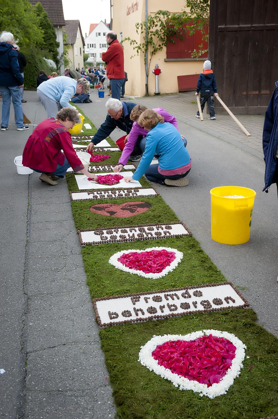 Frauen belegen einen Blumenteppich mit Herzen