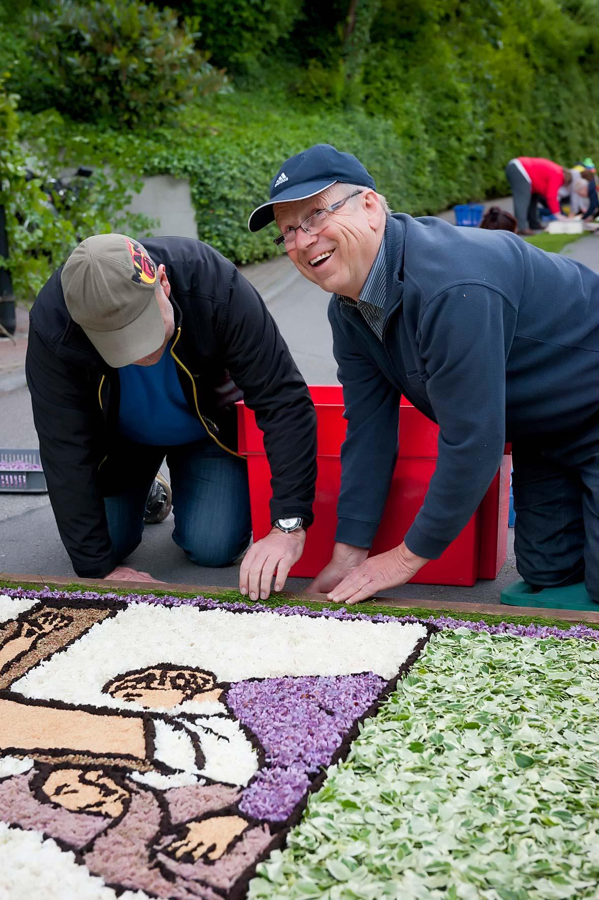 Zwei Männer prüfen mit letzten Handgriffen den Blumenteppich