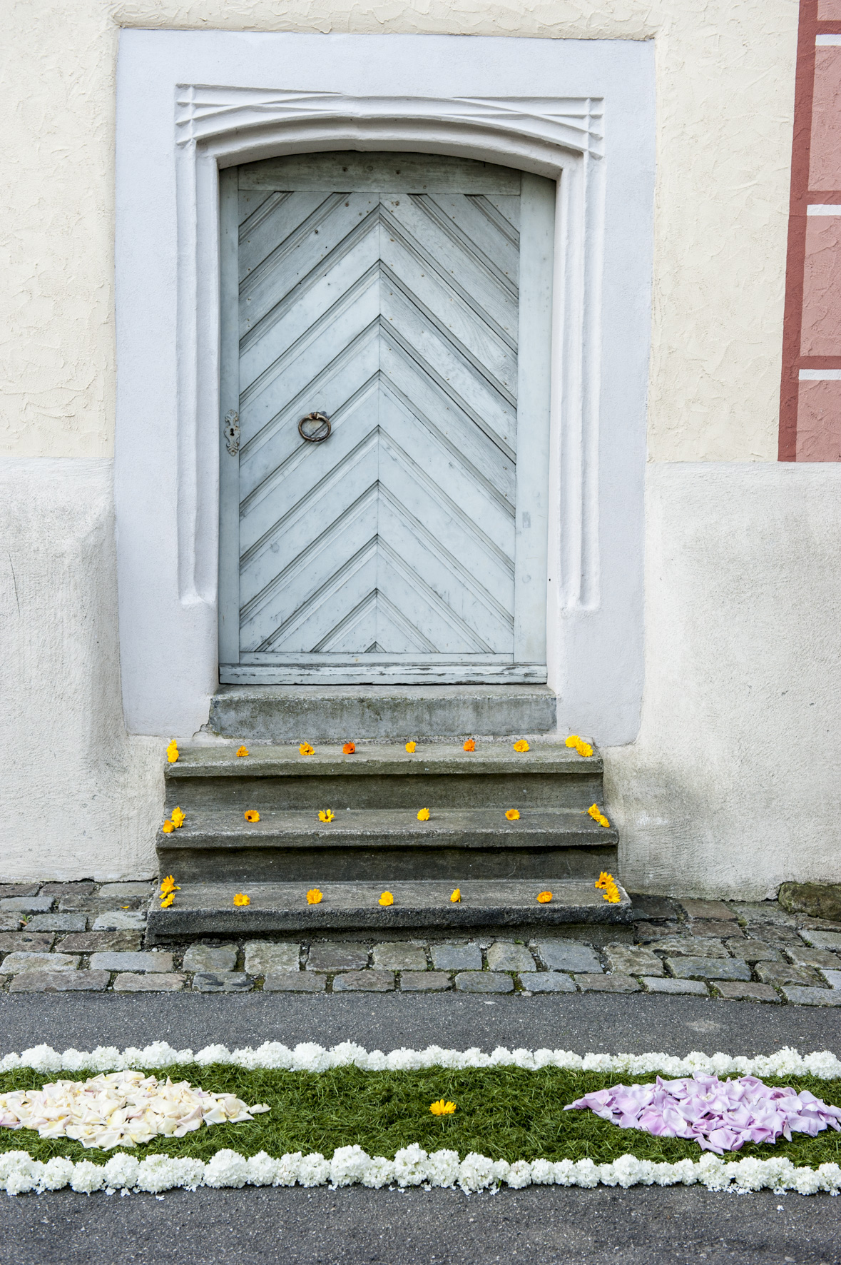 Bluementeppich mit einer mit Blumen verzierten Treppe vor einem Hauseingang